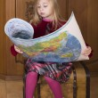 Little girl sits on a chest and considers  world map — Stock Photo