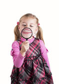 Funny girl showing teeth through a magnifying glass — Stock Photo