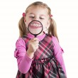 Funny girl showing teeth through a magnifying glass — Stock Photo #36972619