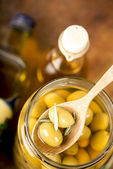 Close up green olives in bank, bottle of olive oil, rosemary — Stock Photo