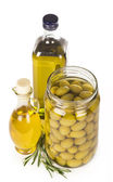 Green olives preserved in bank, bottle of olive oil, rosemary — Stock Photo