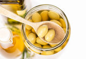Close up green olives preserved in bank, bottle of olive oil, rosemary — Stock Photo