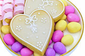 Heart shaped biscuits and sugared almonds. — Stock Photo