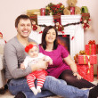 Happy Christmas family near the fireplace — Stock Photo