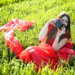 Young lady in red dress with camera on field — Stock Photo