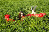 Young lady in red dress lie on field — Photo