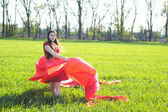 Young lady in red dress on field — Photo