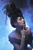 Elegant lady in black with hairstyle in blue smoke — Stockfoto