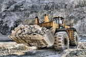 Wheel loader machine unloading rocks — Foto de Stock