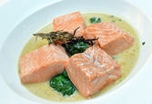 With smoke salmon on spinach — Stock Photo