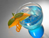 Blue cocktail with ice and orange — Stock Photo