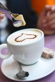 Sugar cube is placed in a cup of cappuccino — Stock Photo
