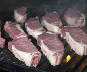 Beef steak raw on an open flame grill — Stock Photo