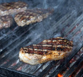 Beef steak cooking on an open flame grill — Stock Photo