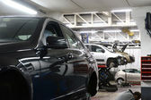 Car in garage with special equipment prepared for repair — Stock Photo