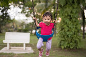 Chinese girl playing on the swing — Stock Photo
