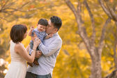 Asian young family having fun outdoors in autumn — Stok fotoğraf