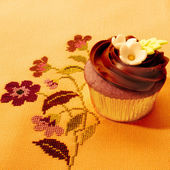 Delicious chocolate muffin on vintage tablecloth — Stock Photo