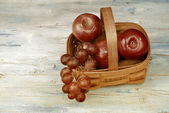 Basket with red apples and grapes — Stock Photo