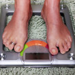 Woman on the weight scale — Stock Photo