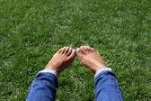 Bare feet in green grass — Stock Photo