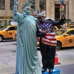 Artist imitating Statue of Liberty and tourist — Stock Photo