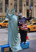 Artist imitating Statue of Liberty and tourist — Stock Photo