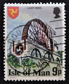 A stamp printed in Isle Of Mann shows The Laxey Wheel is a large waterwheel built in the village of Laxey — Stock Photo
