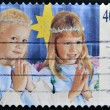 Stock Photo: A stamp printed in Australia shows girls dressed as angels praying