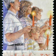 Christmas stamp printed in Australia shows family singing with candles — Stock Photo
