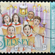 Stock Photo: A christmas stamp printed in Jersey shows children's choir singing come all ye faithful