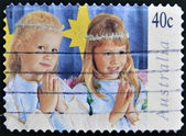 A stamp printed in Australia shows girls dressed as angels praying — Stock Photo