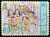 A christmas stamp printed in Jersey shows children's choir singing come all ye faithful — Stockfoto