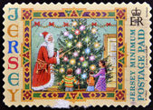 A stamp printed in Jersey shows Santa Claus and children — Stock Photo