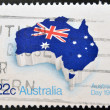 Stock Photo: Stamp printed in Australishows flag of Australiplaced in contour of continent