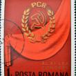 A stamp printed in Romania shows Communist party symbol on red background — Photo