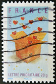 A stamp printed in France shows hearts in a box — Stock Photo