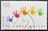 A stamp printed in Germany dedicated to UNICEF, shows colored stains hands — Zdjęcie stockowe