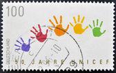 Znaczek wydrukowany w niemczech, poświęcone unicef, pokazuje kolorowe plamy rękach — Zdjęcie stockowe