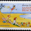 A stamp printed in australia shows greetings from sandy beach — Stock Photo #13190200