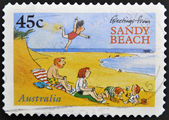 A stamp printed in australia shows greetings from sandy beach — Stock Photo