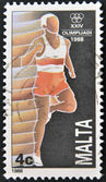 A stamp printed in Malta shows Running — Stockfoto