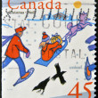 A stamp printed in Canada shows image of children playing in the snow - Stock Photo