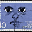 "Stock Photo: Stamp printed in Switzerland dedicated to international federation ""terre des hommes"" shows eyes of child"