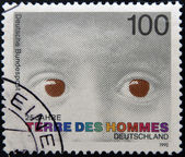 """A stamp printed in Germany dedicated to international federation """"terre des hommes"""" shows the eyes of a child — Stock Photo"""