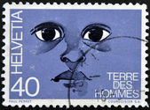 """A stamp printed in Switzerland dedicated to international federation """"terre des hommes"""" shows the eyes of a child — Stock Photo"""