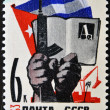 A stamp printed in Russia shows Cuban flag, hands with gun and book — Stock Photo
