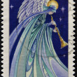 Постер, плакат: A christmas stamp printed in Isle of Man shows angel playing the flute