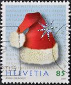 Un noël timbre imprimé en suisse présente chapeau de noël — Photo
