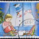 muestra a un sello impreso en Gran Bretaña dedicada a la Navidad, niño tocando la flauta y el muñeco de nieve — Foto de Stock